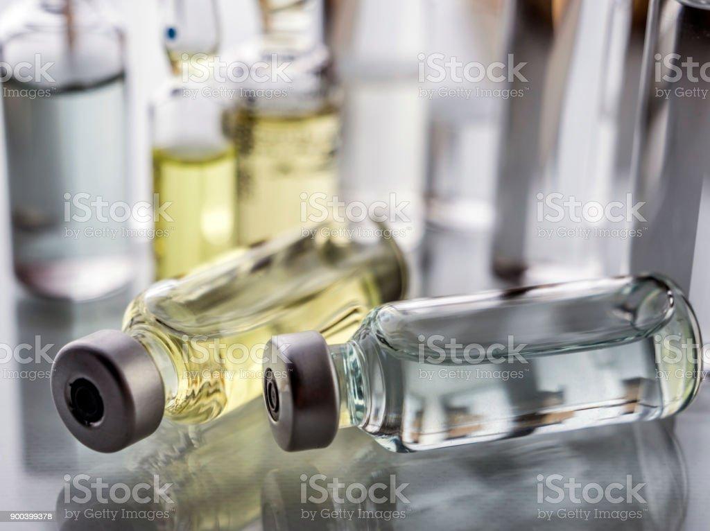 Mehrere Ampullen und Fläschchen in einer Schale mit einem Krankenhaus, Palliativmedizin, Konzeptbild – Foto