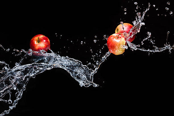 Several apple flying in space with the water stock photo