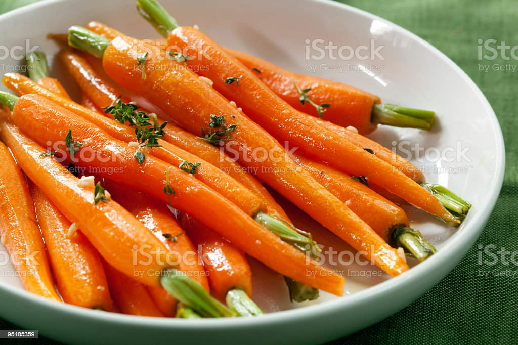 Several baby carrots in a white bowl with herbs stock photo