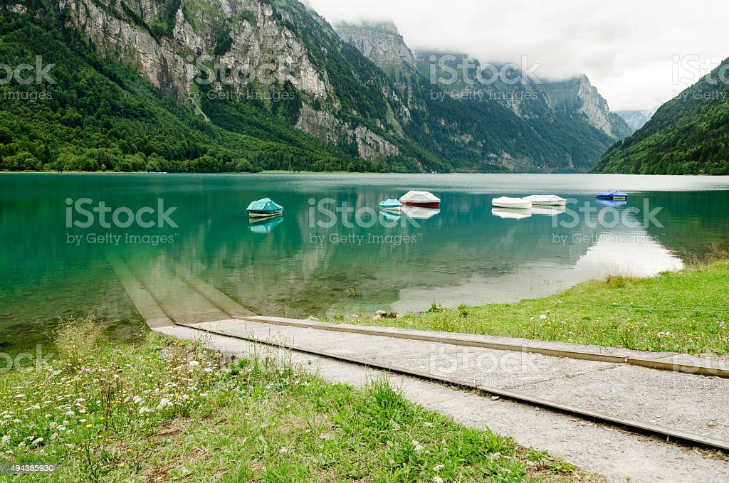 Several boats floating on a greenish mountain lake in Switzerland stock photo