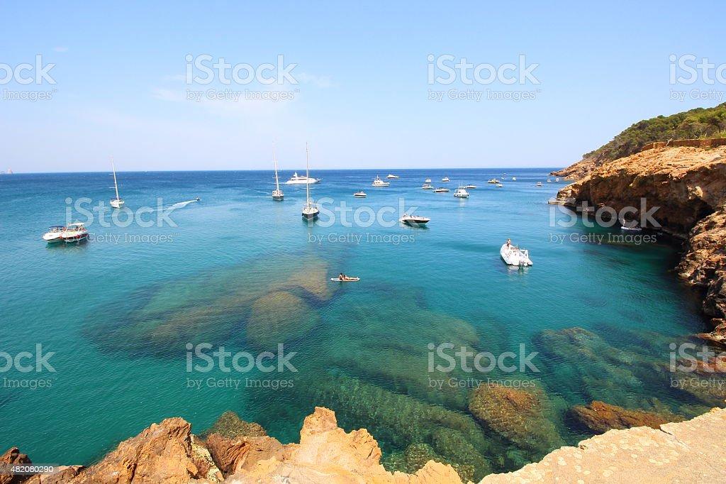 Several boats sail through crystal waters stock photo