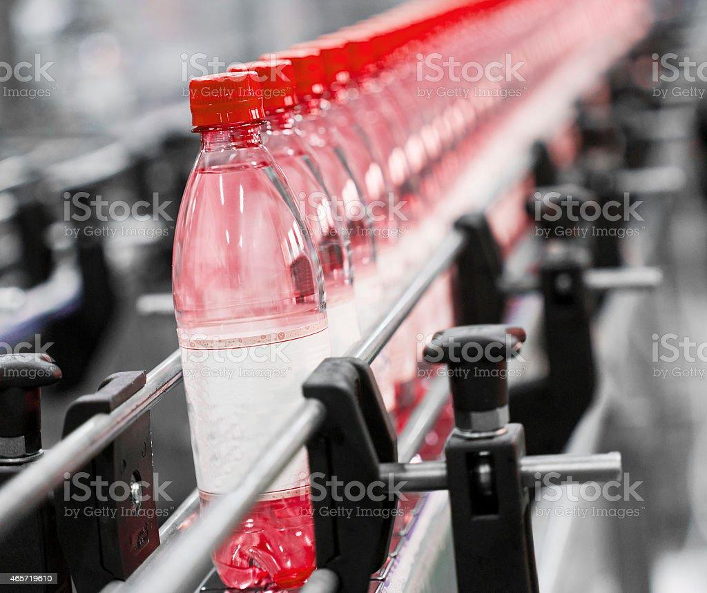 Several bottled drinks on a conveyer belt stock photo