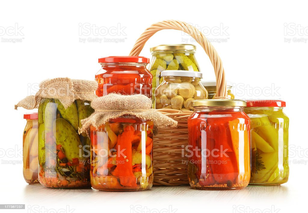 Several bottles of pickled vegetables in wicker basket royalty-free stock photo