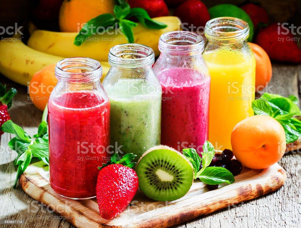Nombreuses bouteilles avec des fruits et des jus de fruits - Photo