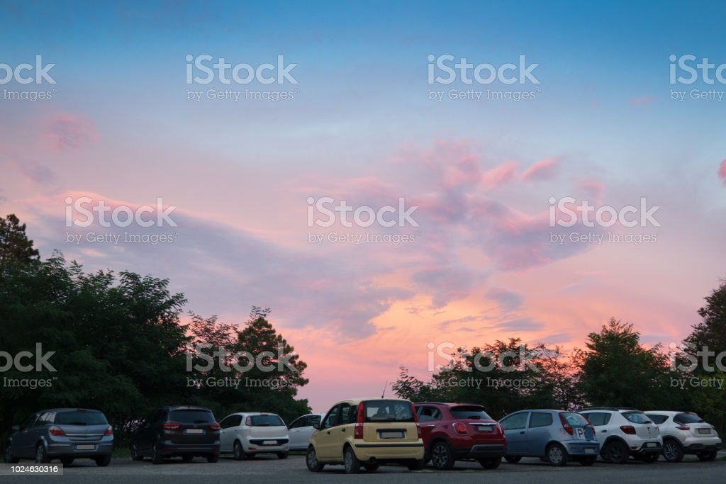 several cars are parked at the evening in a scenic natural location