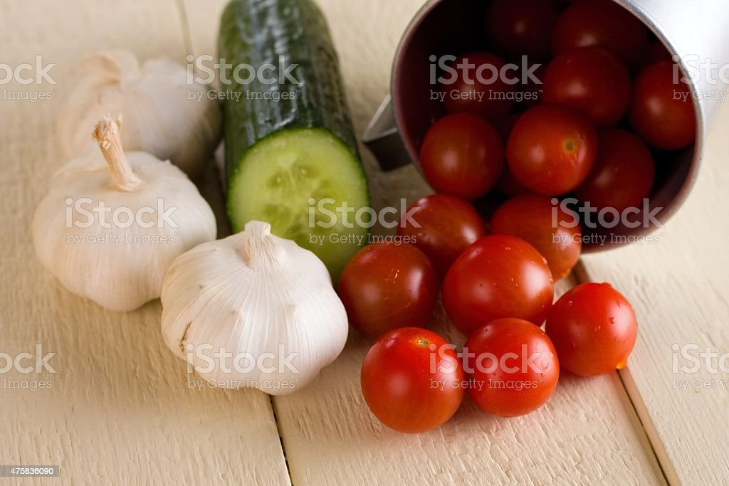Several cherry tomatoes and garlic with cucumber on white board stock photo