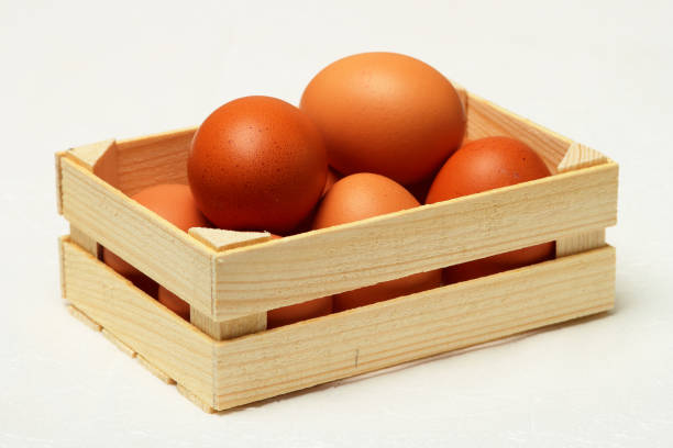 Cтоковое фото Several chicken eggs in wooden box.