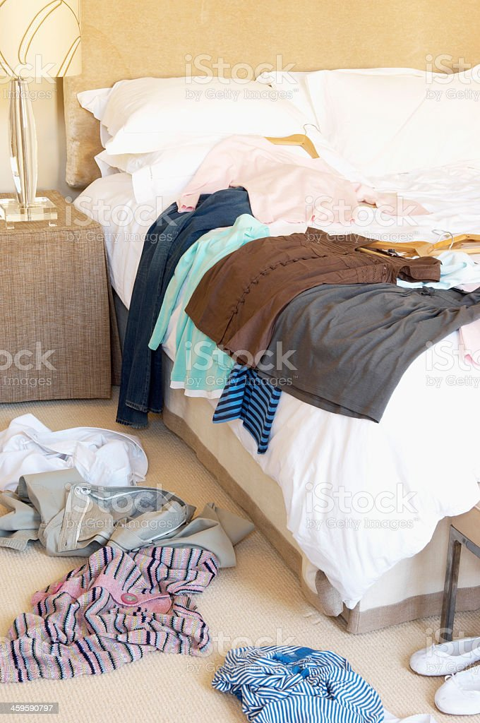 Several clothes scattered on the hotel floor and bed - Royalty-free Bed - Furniture Stock Photo