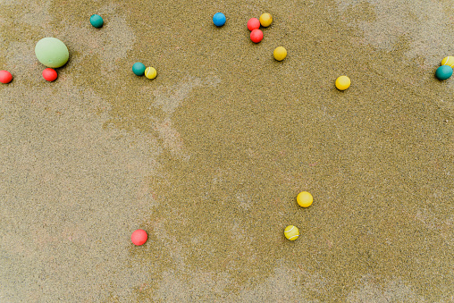 Several colored balls on the green floor of a school, views from above, background with copy space.