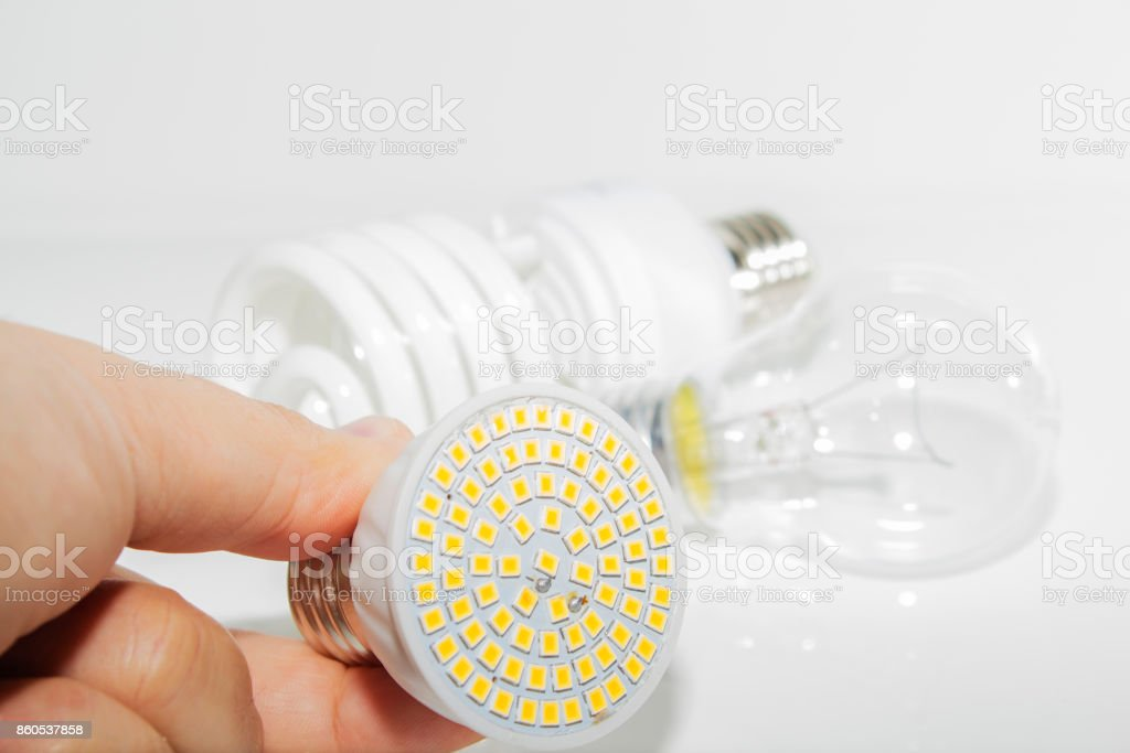 Several different led bulbs and compact fluorescent lamps and the male hand on a light background. stock photo