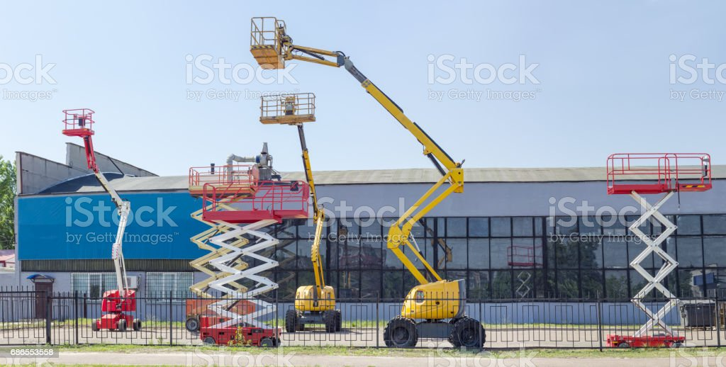 Several different scissor and articulated boom wheeled lifts stock photo