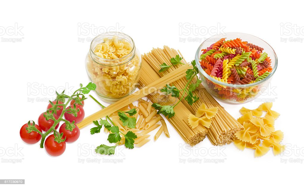 Several different uncooked pasta, sprigs of parsley and cherry t stock photo