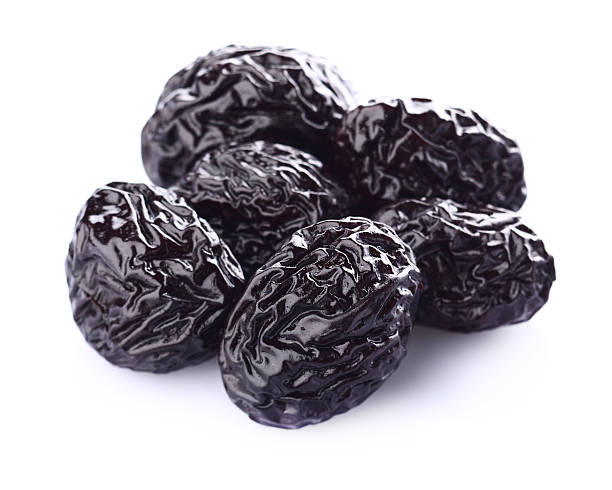 Several dried prunes on a white background stock photo