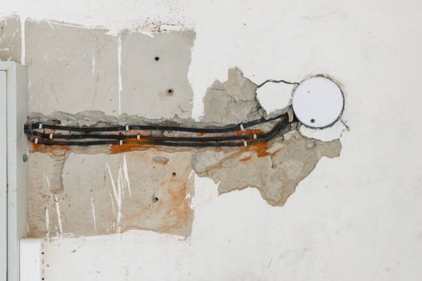Several electrical cables are routed in the damaged wall stock photo