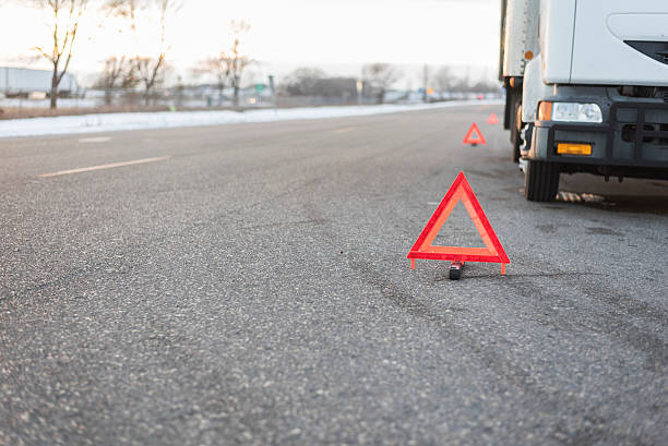 several emergency triangles by truck on road several bright red emergency triangles placed down road by truck parked to the side. medium group of objects stock pictures, royalty-free photos & images