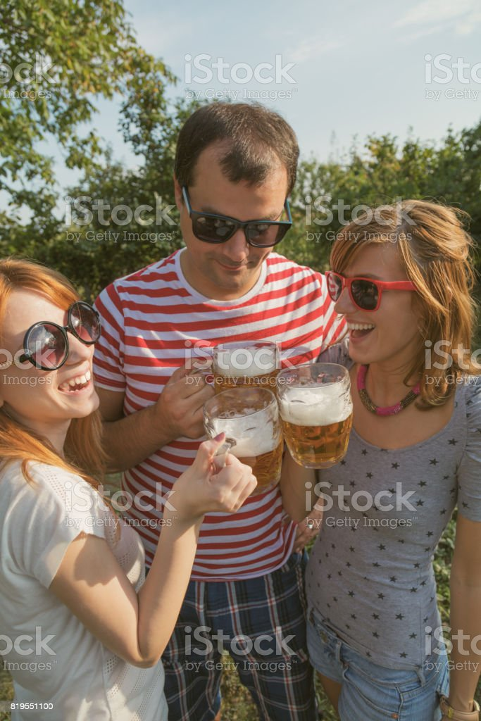 Several friends enjoying outdoors with the beer. stock photo