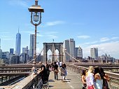 New York City, New York, United States -June 25th, 2014: Several groups of people crossing the pedestrian walkway of the Brooklyn Bridge which connects lower Manhattan to Brooklyn, in New York.