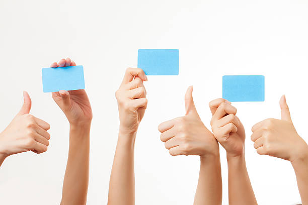 several hands hold blank business cards on white background - gift voucher or card stock photos and pictures
