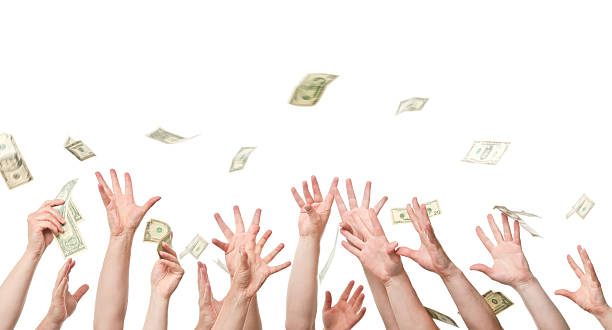 Several hands reaching out to grab dollars raining stock photo
