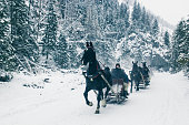Zakopane, Poland, February 10, 2018, Several harnesses of a sleigh drawn by horses are riding along a snow-covered road in the mountains, people are sitting on a sleigh