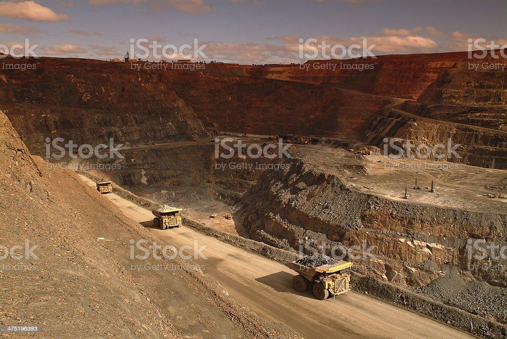 Several haul trucks carrying ore in an open cut mine. stock photo