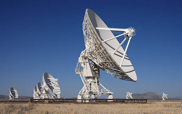 Several huge radio telescopes out in a desert pointed at sky