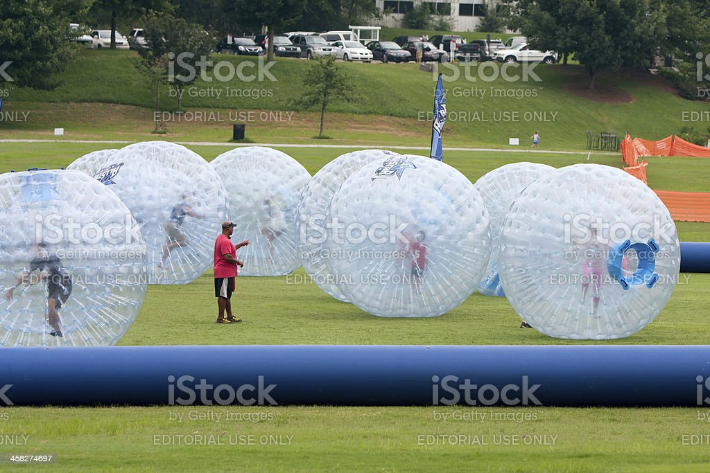 Several Kids Roll Around In Large Zorbs At Summer Festival stock photo