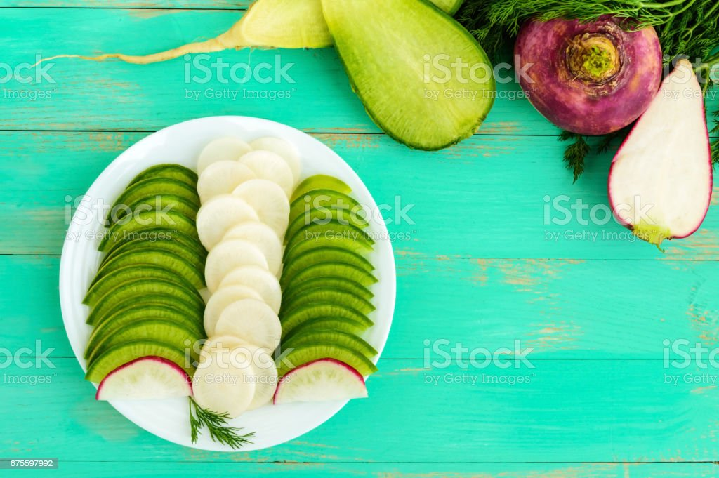 Several kinds of radish sliced on a white plate on a light wooden background. The top view stock photo
