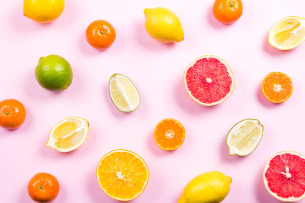 several kinds of whole and cut citrus on a pink background - agrume foto e immagini stock