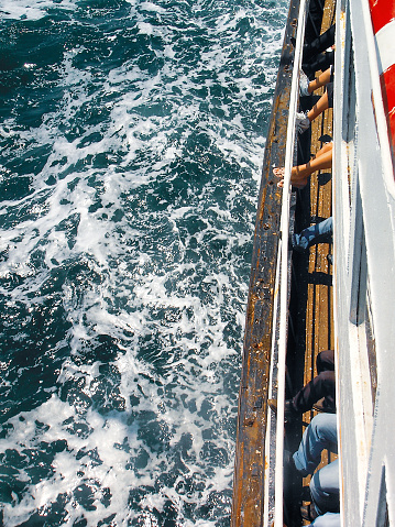 Istanbul, Turkey - June 25, 2006: vertical view of several people on one side of a passenger ship in summer time and fluctuating sea waves on Marmara
