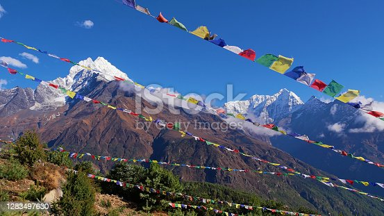 istock Several lines of colorful Buddhist prayer flags flying in the wind above Namche Bazar, Khumbu, Himalayas, Nepal with majestic mountain panorama in background. 1283497630