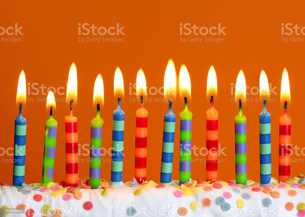 Several lit candles on birthday cake stock photo