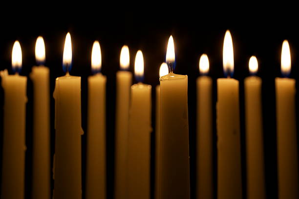 Several Lit White Candles Against Black Background Several tall candles lit in a dark room. medium group of objects stock pictures, royalty-free photos & images