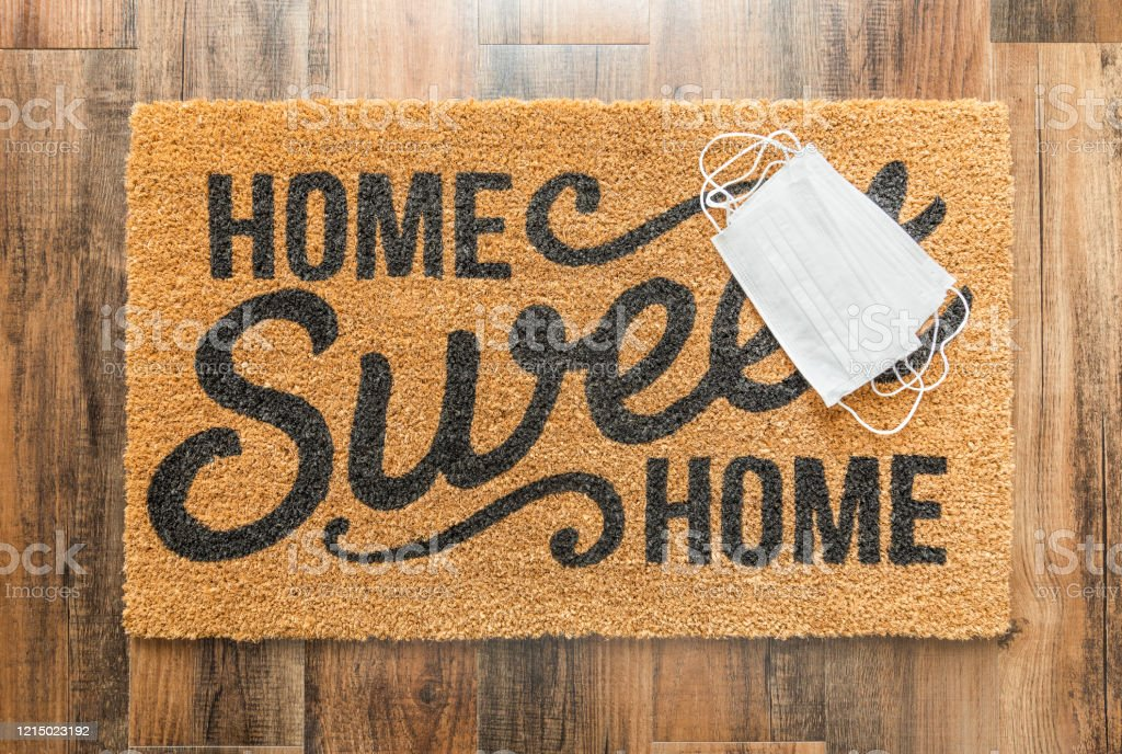 Several Medical Face Mask Rests on Home Sweet Home Welcome Mat Amidst The Coronavirus Pandemic Several Medical Face Mask Rests on Home Sweet Home Welcome Mat Amidst The Coronavirus Pandemic. Blank Stock Photo
