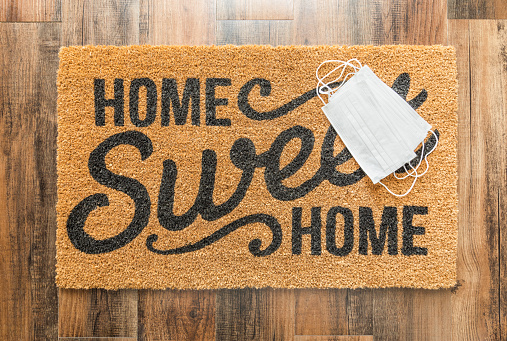 Several Medical Face Mask Rests On Home Sweet Home Welcome Mat Amidst The Coronavirus Pandemic Stock Photo - Download Image Now