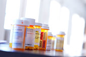 Several prescription medication bottles sit on a table. Light pours in through the windows in the background bathing the room with a soft glow.  The image is photographed with a very shallow depth of field.