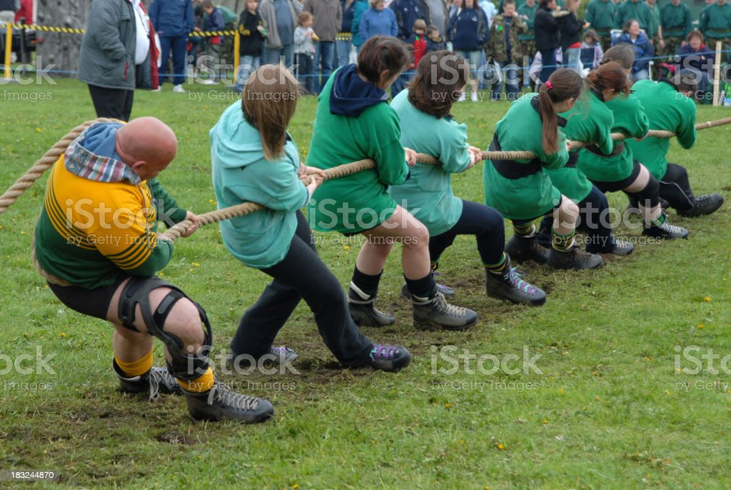 Several men pulling a large rope in tug of war stock photo