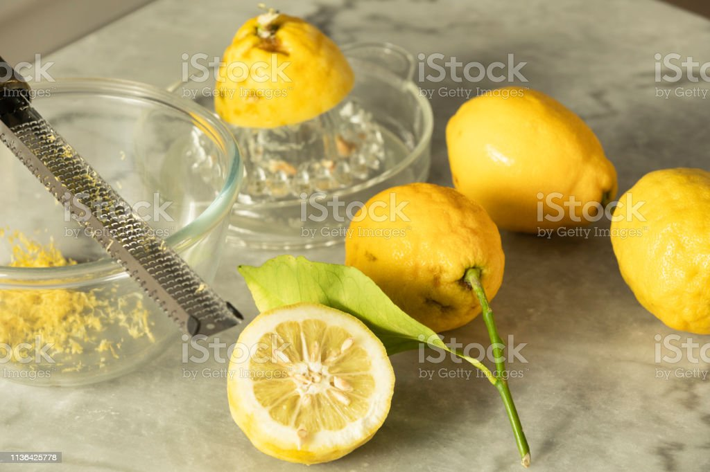 """Several Menton lemon, grater and Lemon's Zest Several lemons of Menton, one of which is cut in half. There is a bowl with lemon zest and an utensil for making lemon juice. the photograph was taken with natural light indoors in a kitchen. The Menton Lemon has a softer taste, more intense aromas and a moderate acidity that can not be found anywhere else. It has been awarded the European label since 2015 """"Protected Geographical Indication"""" (PGI). Alpes-Maritimes Stock Photo"""