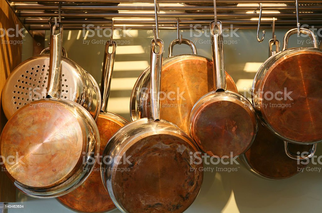 Several metal pots hanging from an overhead pot rack stock photo