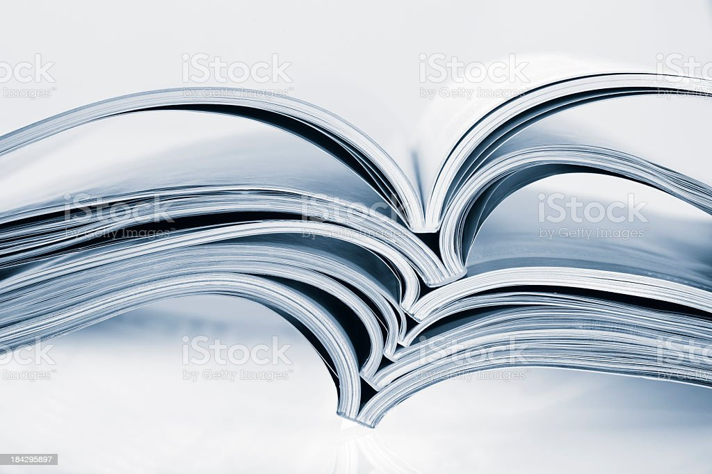 Several open magazines in a stack stock photo