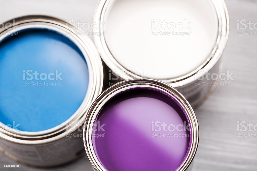 Several opened cans with paint inside. stock photo