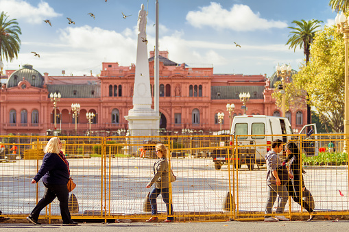 Several passers-by walk in the morning between the renovation works of the Plaza de Mayo in front of the Casa Rosada (Government Palace)
