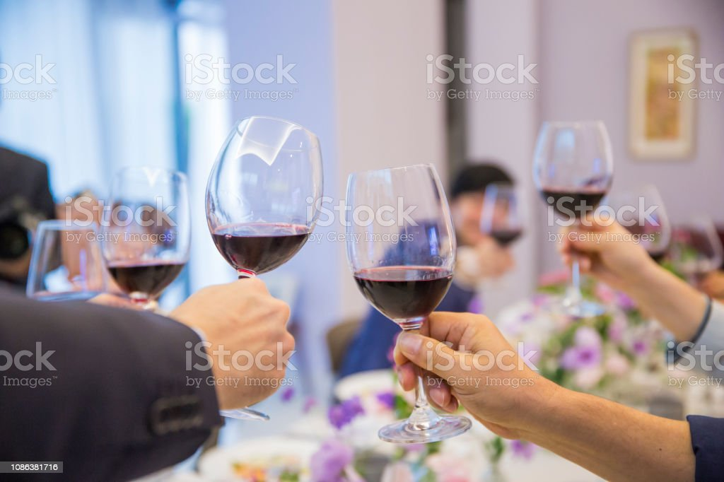 Several people are toasting a glass of red wine at the Party table...