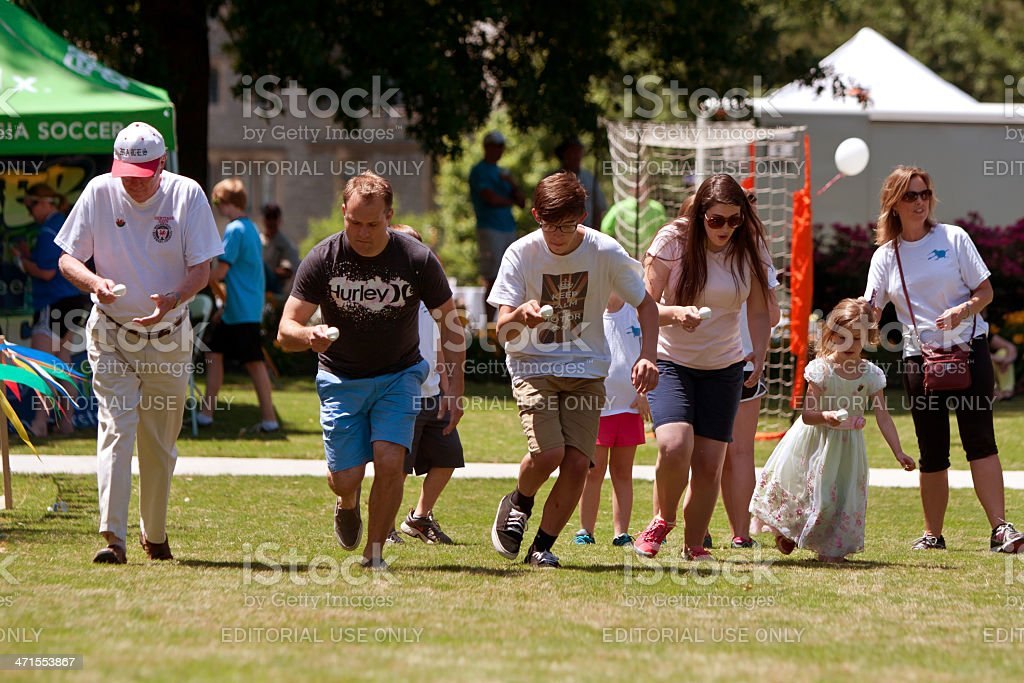 Several People Compete In Egg And Spoon Race At Festival stock photo