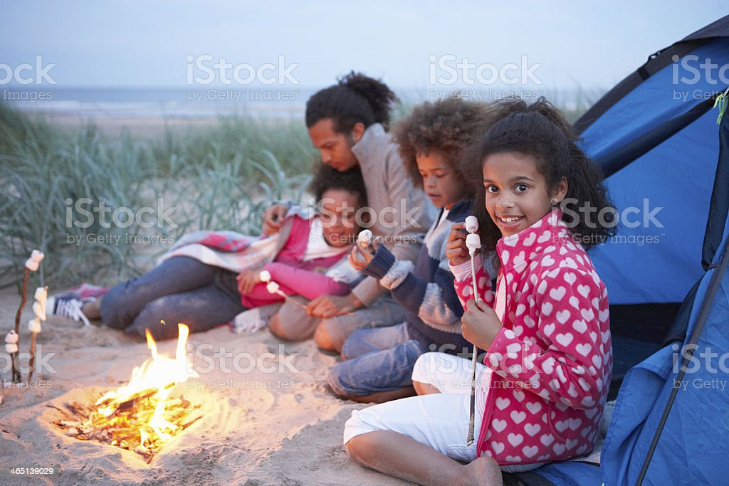 Several people outside of a tent gathered around a fire stock photo