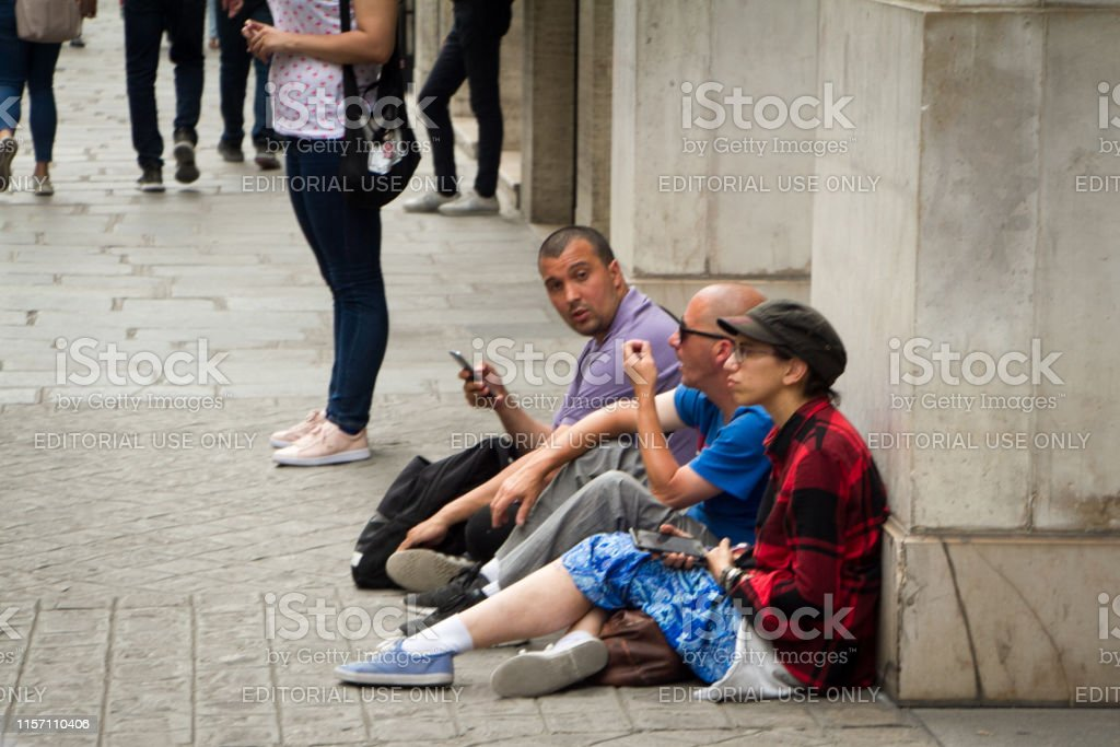 Several people sit on the sidewalk in Paris and talk