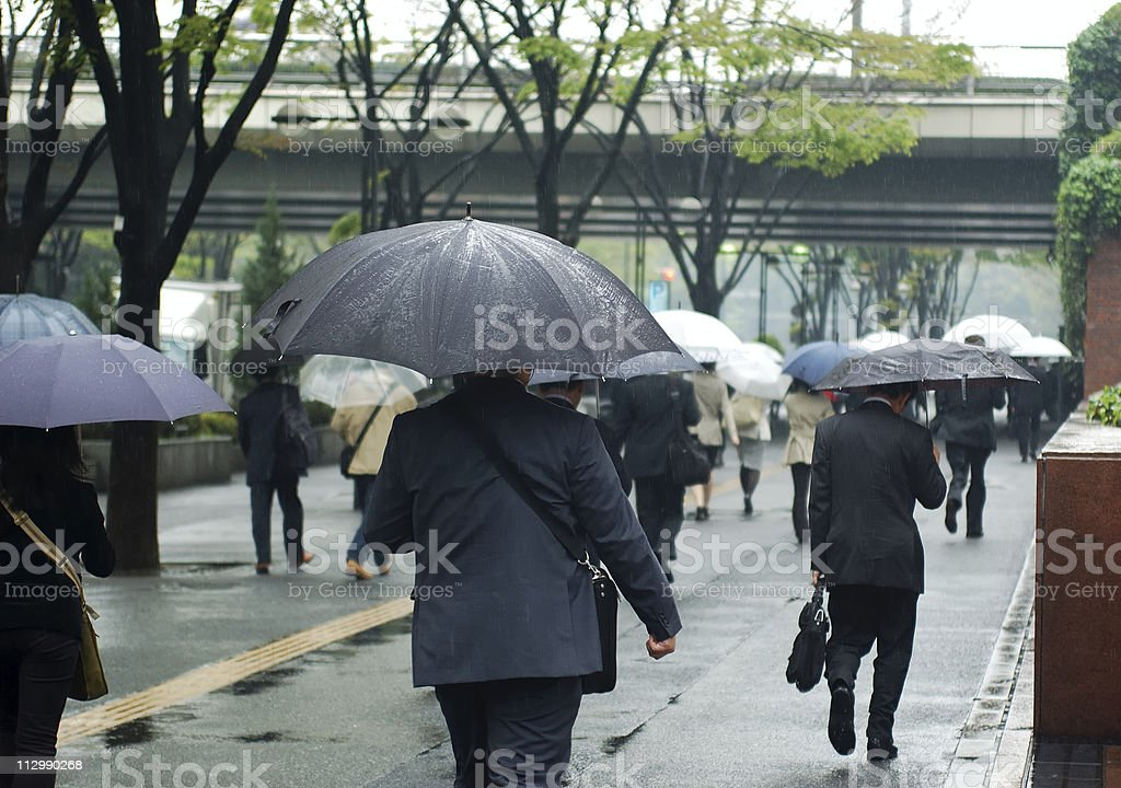 Several people with umbrellas commuting in the rain stock photo