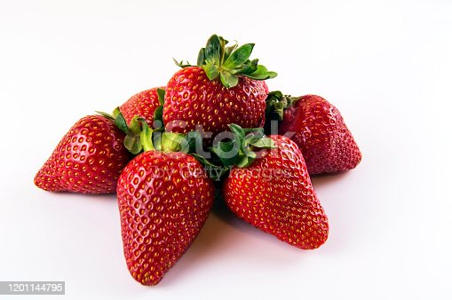 Several pieces of a big red strawberry on a white background.