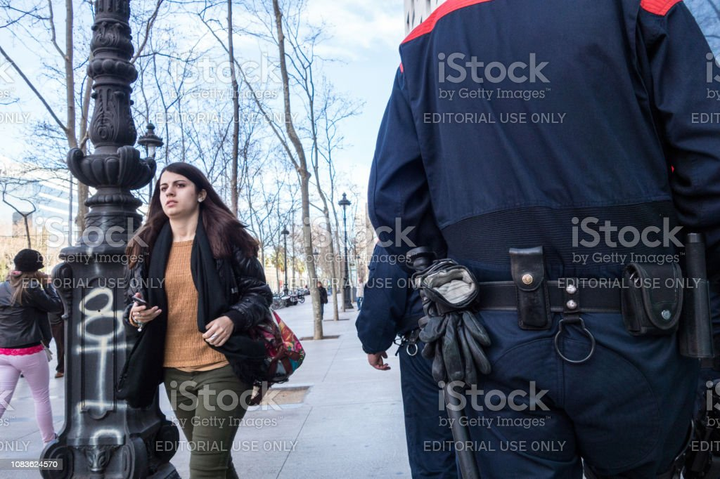 Several catalan policemen , carrying truncheons, handcuffs, gloves...