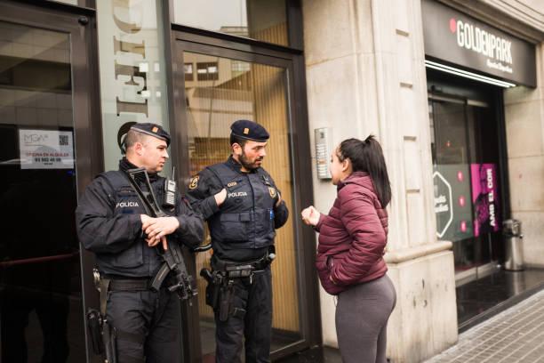 Mehrere Polizisten und andere Menschen laufen entlang einer Straße. Die Frau bittet die Adresse zu ihnen. – Foto